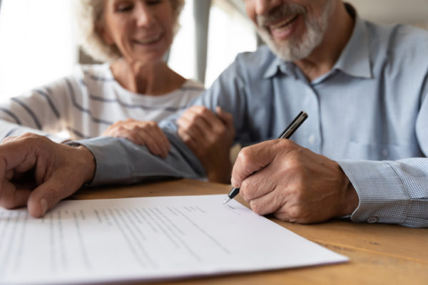 Older couple smiling as the man signs paperwork.