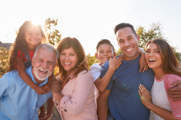 Multigenerational family smiling for a group photo outside on a sunny day.